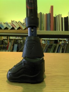 A blue walking stick tries on a rainboot and a black sneaker