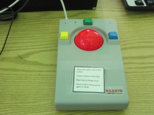 a red trackball with yellow, green, and blue buttons
