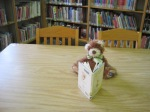 A fuzzy brown bear wearing a green  checked bowtie and reading Beatrix Potter books